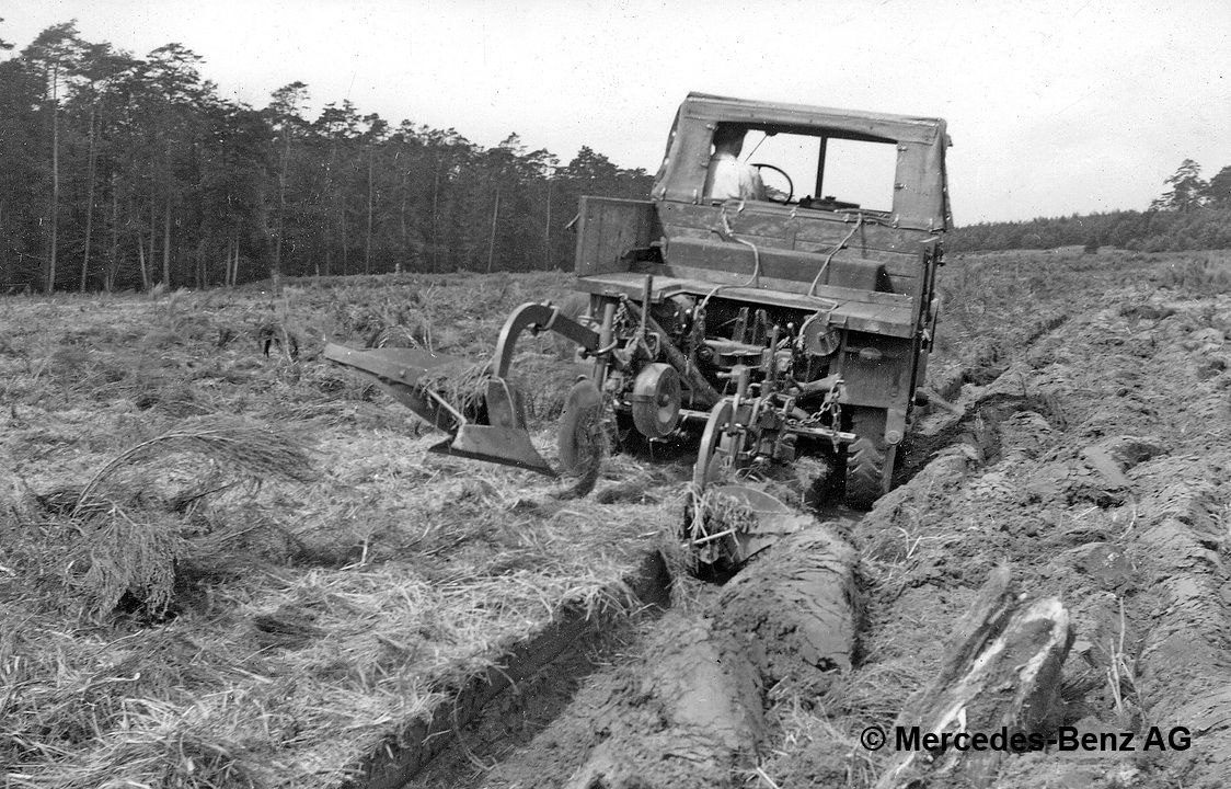 unimog u25, model series 2010 with plough cultivating soil