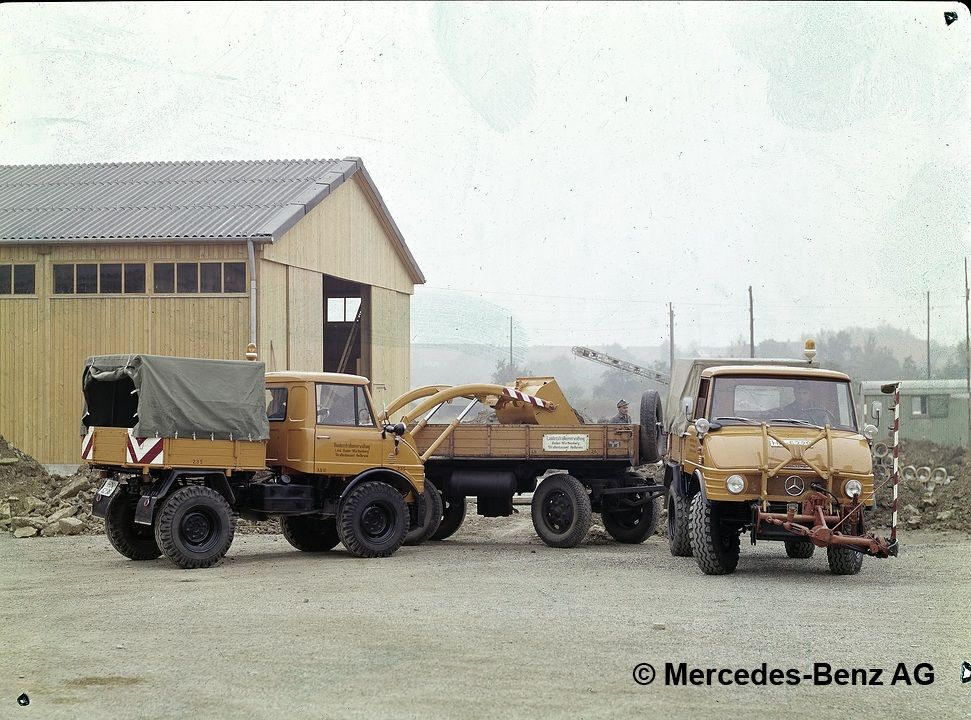 unimog, model series 421 with front loader transferring bulk material to a unimog, model series 421 with mower boom and trailer